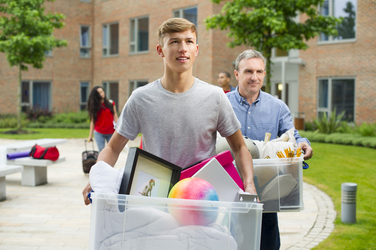 College student carrying boxes into dorm with dad in background.