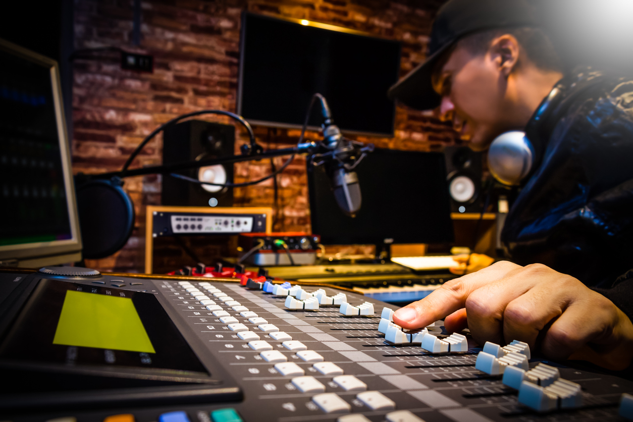 Male sound engineer working on a sound board as part of his music career.