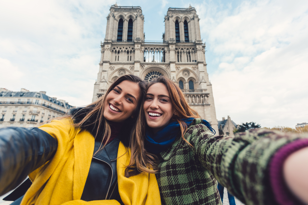Two young women taking selfie in front of Notre Dame in Paris.