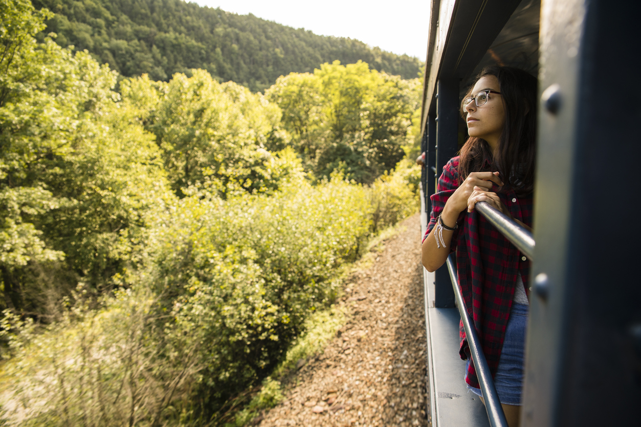 Young female traveler leaning out a window on a train.