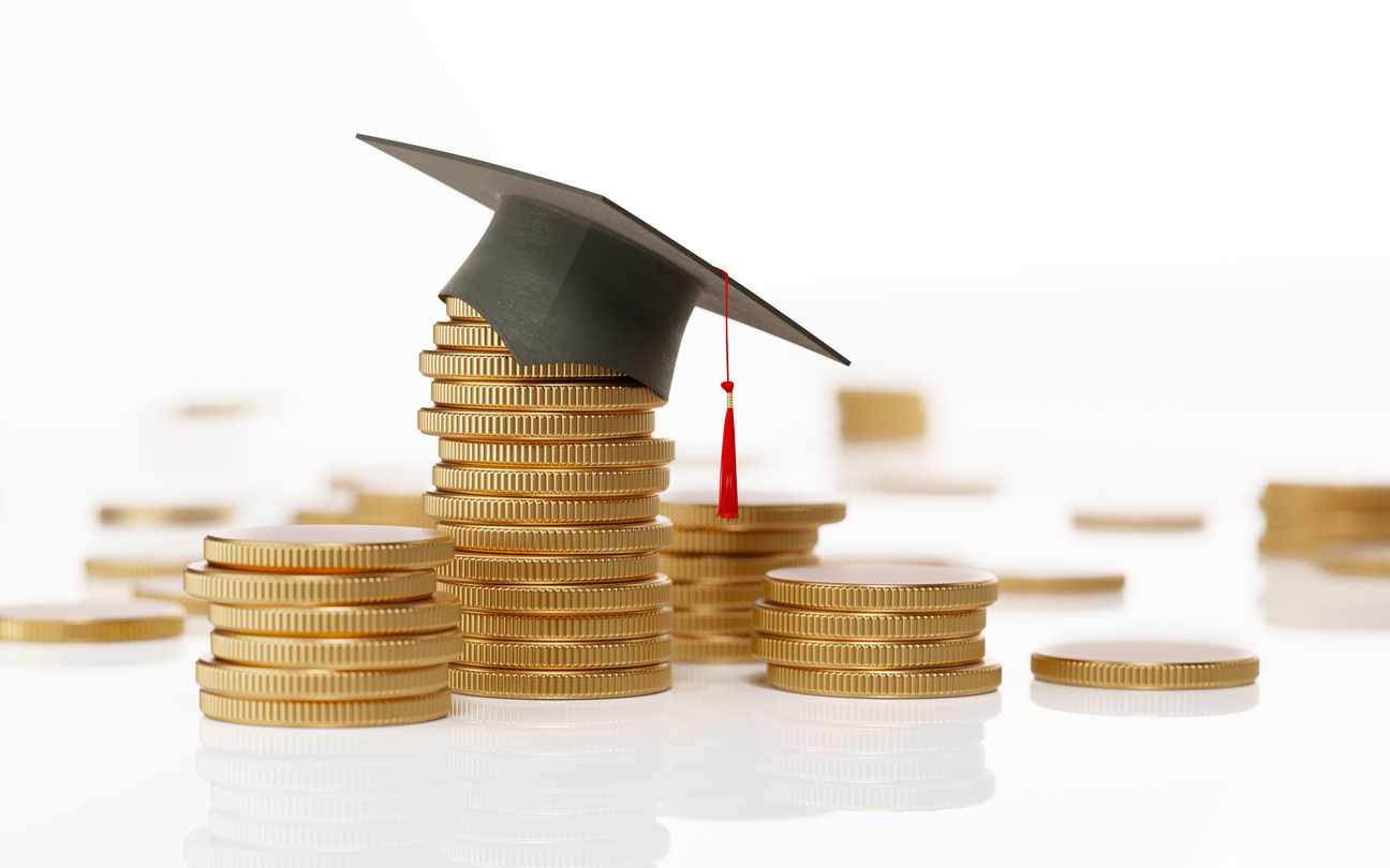 Pile of coins with a miniature graduation cap on top.