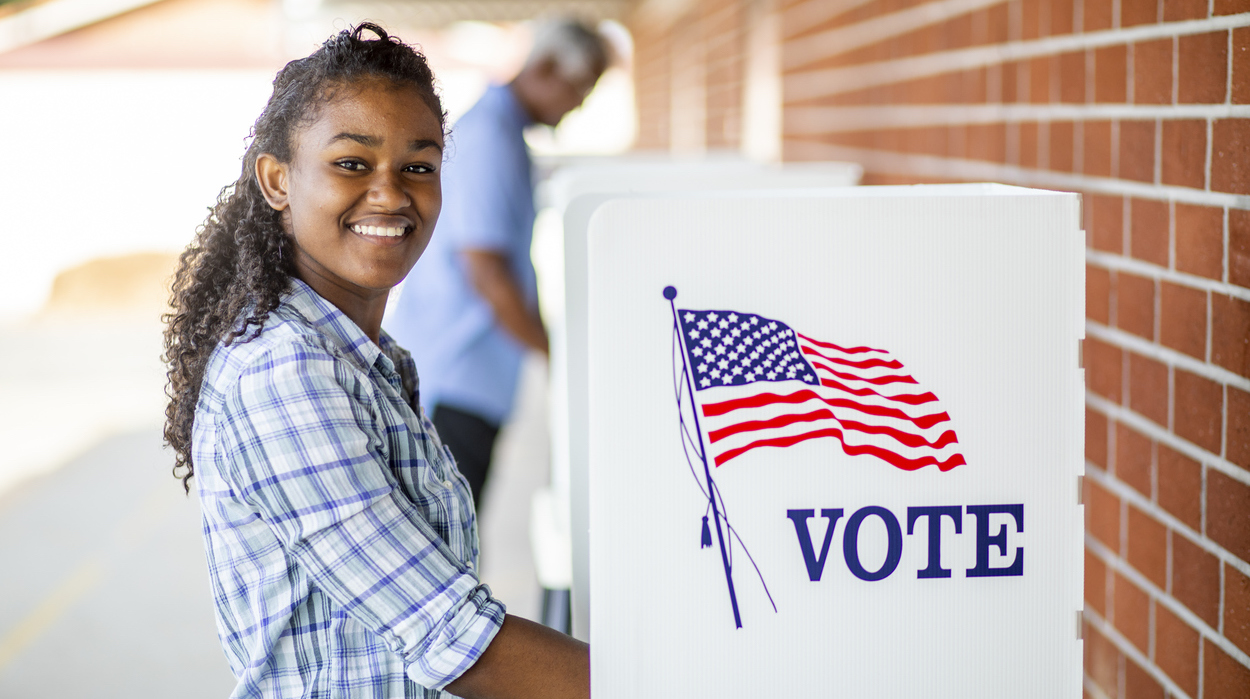 Young woman standing at an outdoor voting booth