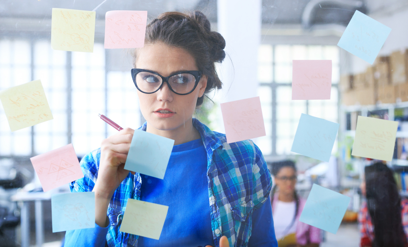 Young woman looking confused at post-it notes on a glass wall.