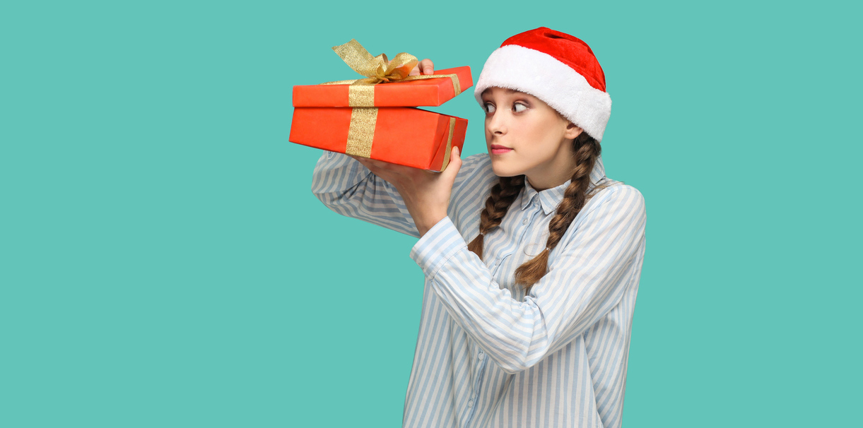 beautiful girl in striped light blue shirt in red christmas cap standing holding red gift box, unboxing and looking inside