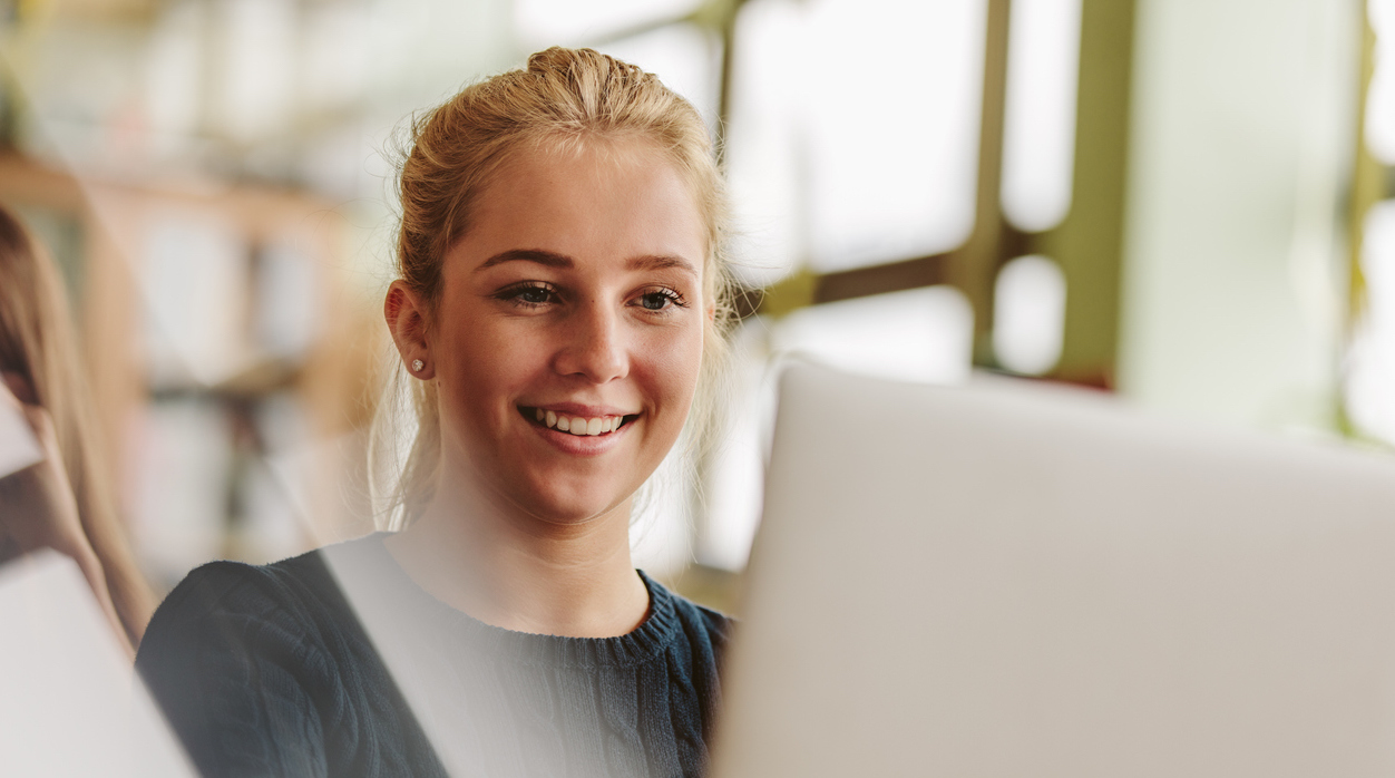 Young blonde woman studying at computer.