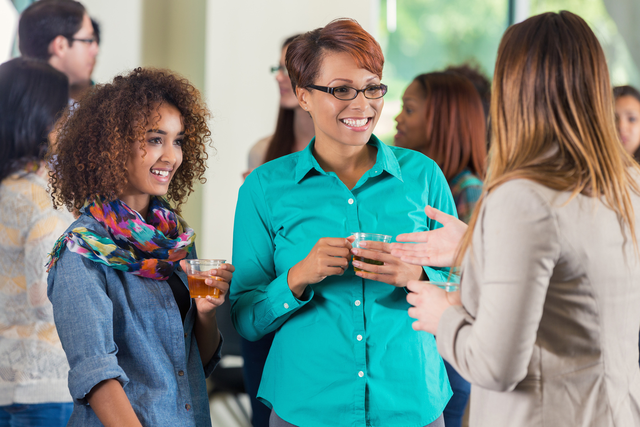 Mother and daughter at college orientation party talking with female professor.