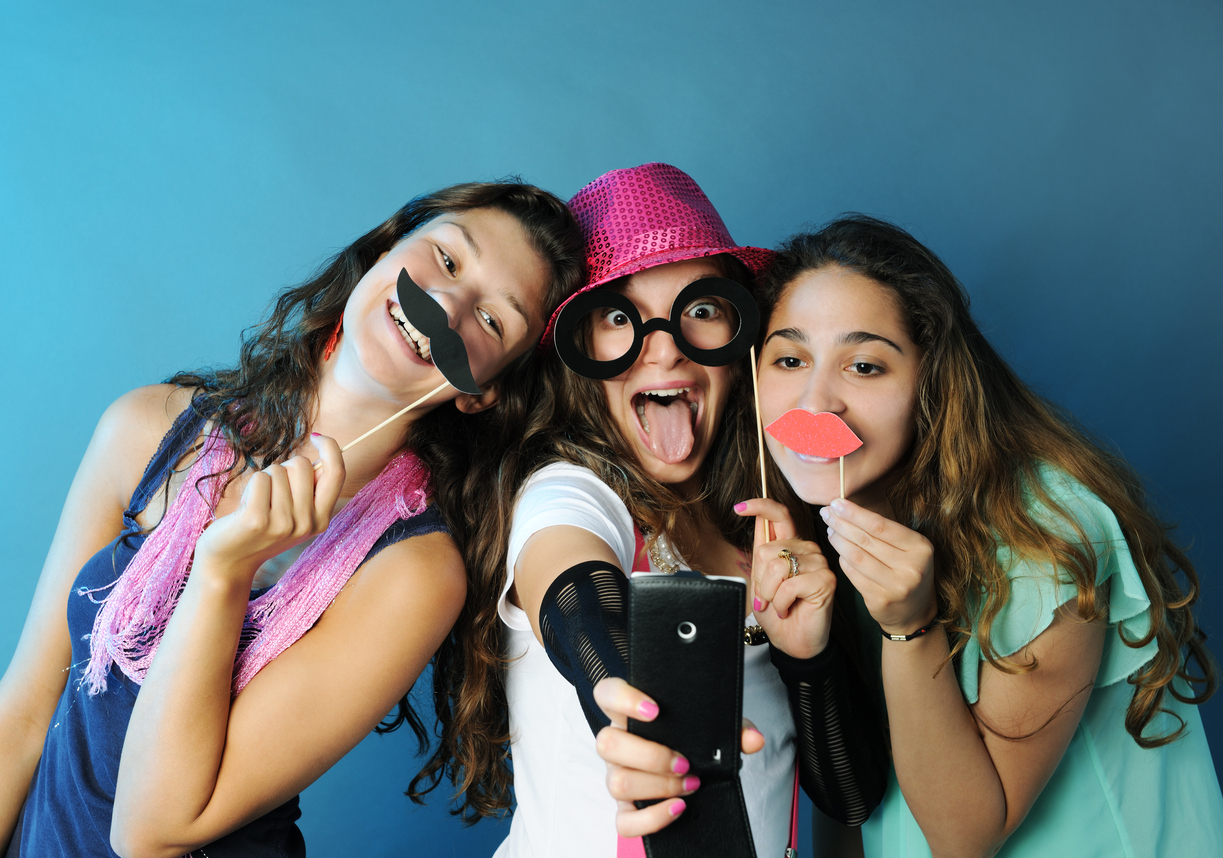Teenage girls acting silly with mustaches and taking a selfie